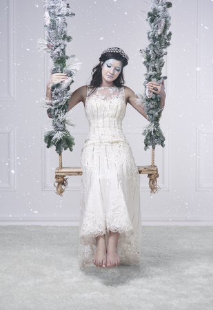 Woman in snow queen costume on swing