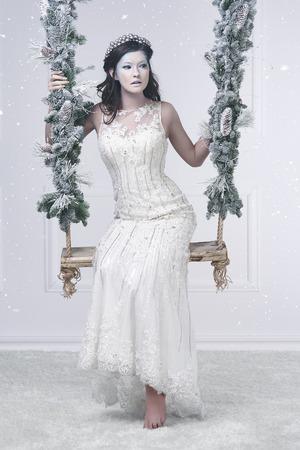 Beautiful snow maiden on swing  Stock Photo