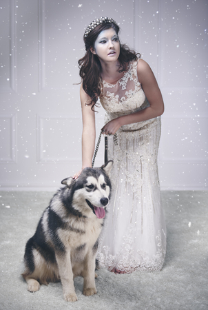 Pretty ice queen with dog among snow falling