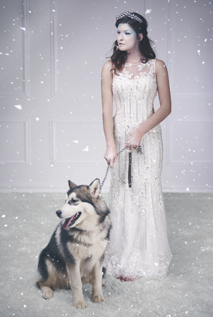 Portrait of ice queen and sled dog among snow falling