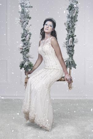 떨어지는 눈 가운데 스윙에 예쁜 얼음 여왕