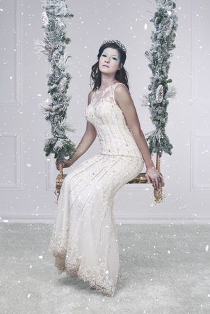 Pretty ice queen on swing among falling snow  Stock Photo