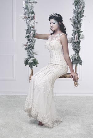Vrouw in witte jurk en ijzig make-up op schommel