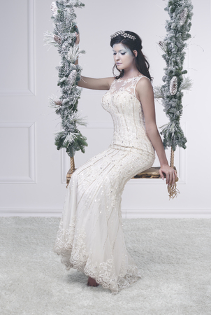 Woman in white dress and frosty make up on swing Stock Photo - 93467420
