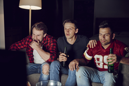 Men friends watching american football in the evening