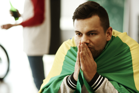 Nervous football fan with flag praying Stock Photo