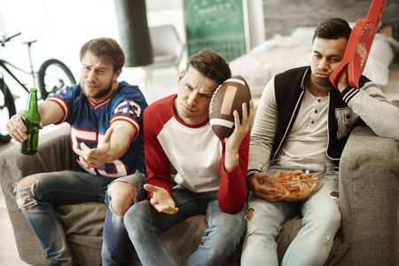 Disappointed football fans at home