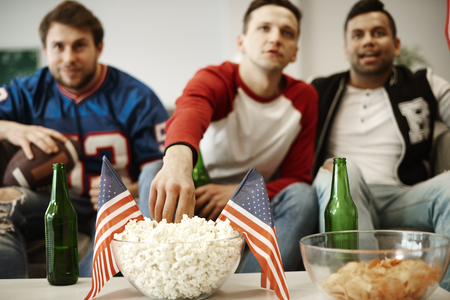 Unrecognizable football fans snacking at home Stock Photo