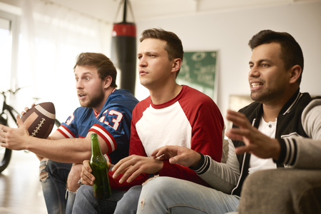 Unhappy men while watching american football Stock Photo