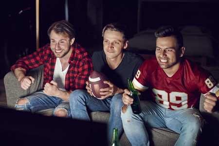 Stressed men watching match in concentration Stock Photo
