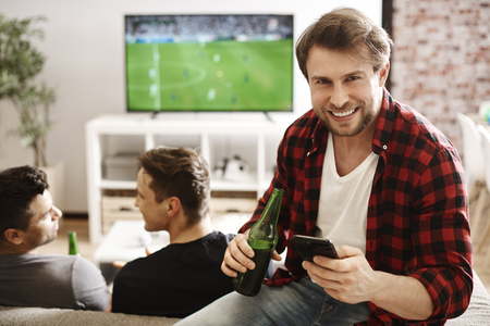 Football fans with mobile phone and beer  Stock Photo