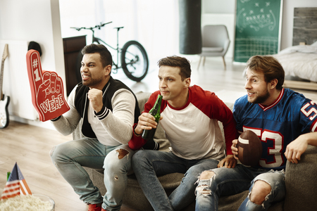 Male acquaintances supporting their football team  Stock Photo