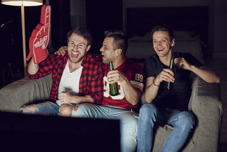 Men with foam hand and beer at football party
