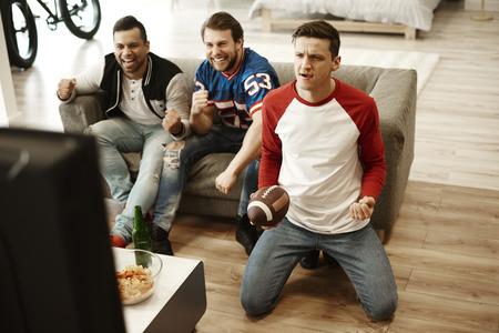 Male friends watching American football