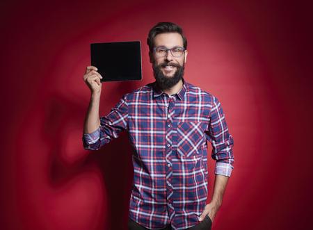 Excited man showing digital tablet