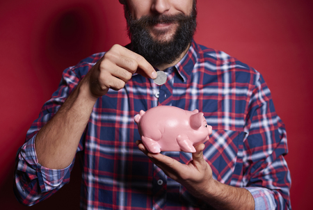 Unrecognizable man inserting coin into piggy bank Stockfoto