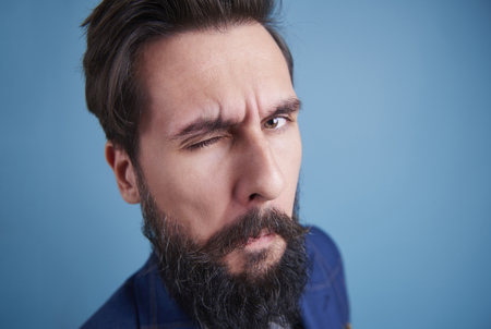 Handsome man with beard winking