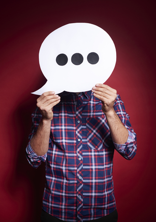 Man holding thinking bubble in front of his face