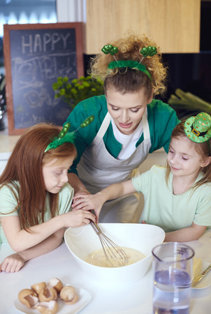 Children with wire whisk baking cupcakes at kitchen