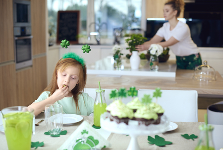 Girl eating cookie at table
