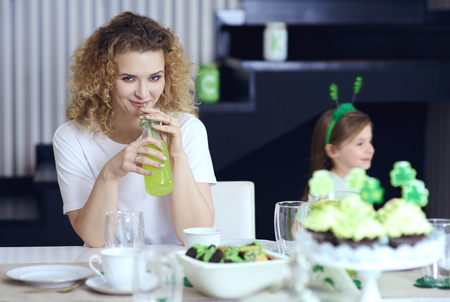 Woman drinking cocktail at Saint Patricks Day party Stock Photo