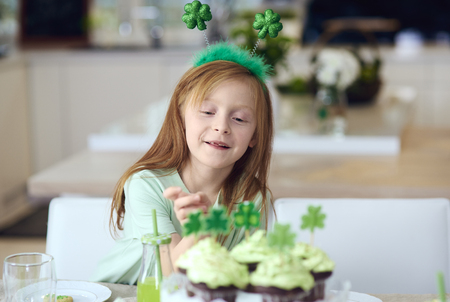 Cheerful girl reaching for cupcake