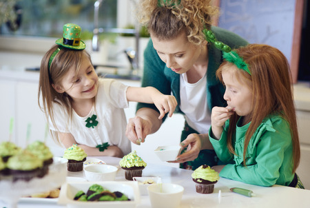 Woman with children decorating cupcakes   Stock Photo