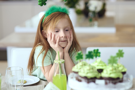 Child looking at delicious cupcakes
