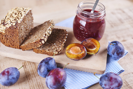 Homemade plum jam with fresh bread on cutting board