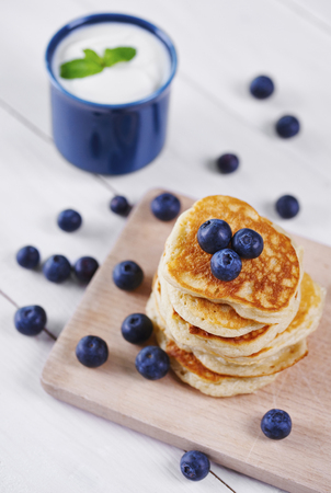 Pancakes with blueberry on cutting board