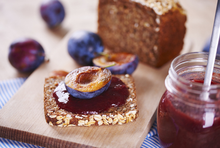 Sandwich with fresh plum jam on cutting board Stock Photo