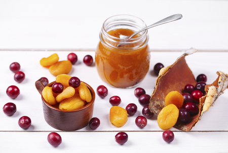 Jar of apricot jam on wooden table