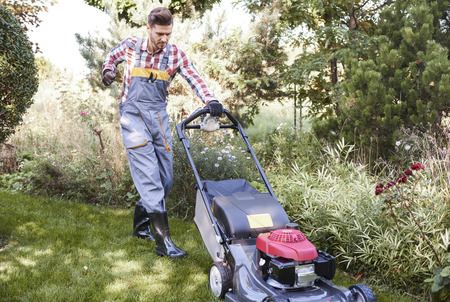 Gardener turning on a mower   Stock Photo