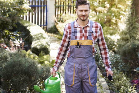 Gardener in uniform holding watering can Stock Photo