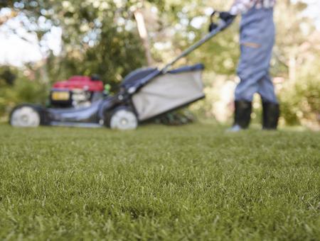 Defocused gardener pushing lawn mower