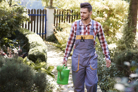 Man with  watering can at garden  Stock Photo