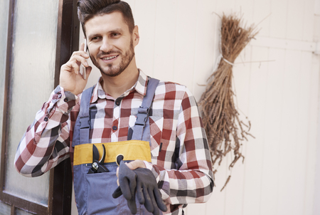 Cheerful gardener talking by mobile phone