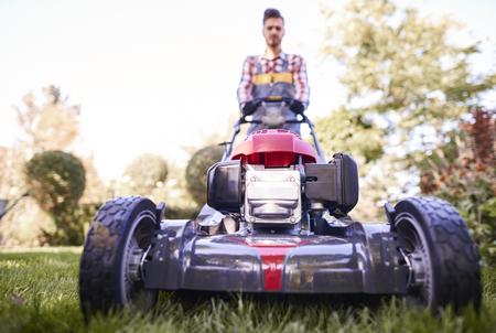 現代の芝刈り機を押すデフォーカス庭師