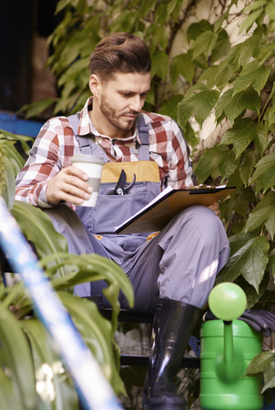 Gardener or farmer with clipboard and coffee