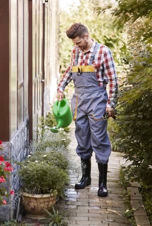 Full length portrait of gardener watering flower