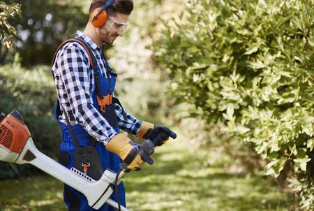 Gardener with weedwacker cutting the grass