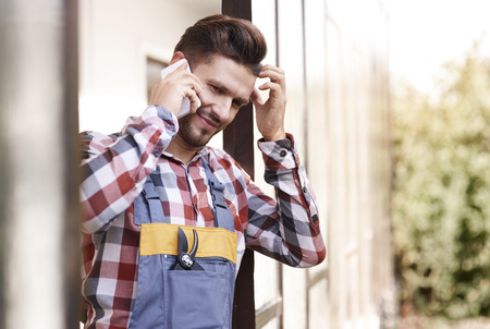 Disconcerted gardener talking by mobilephone