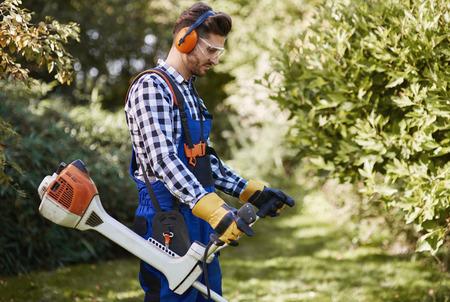 Man with weedwacker cutting the grass