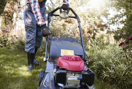 Unrecognizable gardener turning on mower
