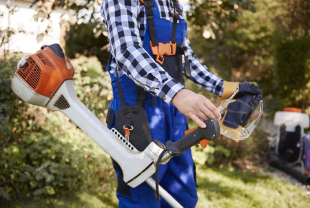 Unrecognizable gardener with modern weedwacker Stock Photo