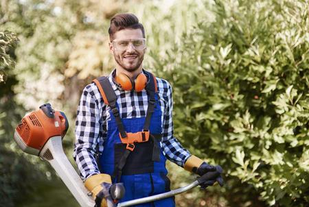 Portrait of man working with weedwacker