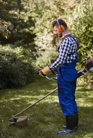 Busy man using a weedwacker at garden