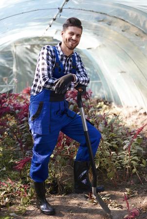 Gardener leaning against a shovel  Stock Photo