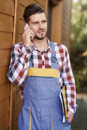 Serious gardener talking by mobile phone  Stock Photo