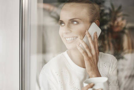 Happy businesswoman looking through window and talking by mobie phone  Stock Photo
